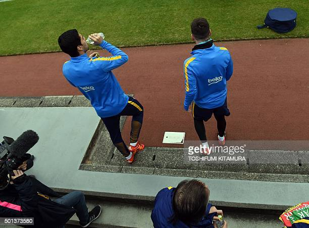 FC Barcelona forwards Lionel Messi and Luis Suarez enter the pitch during their training session at the Club World Cup football tournament in...