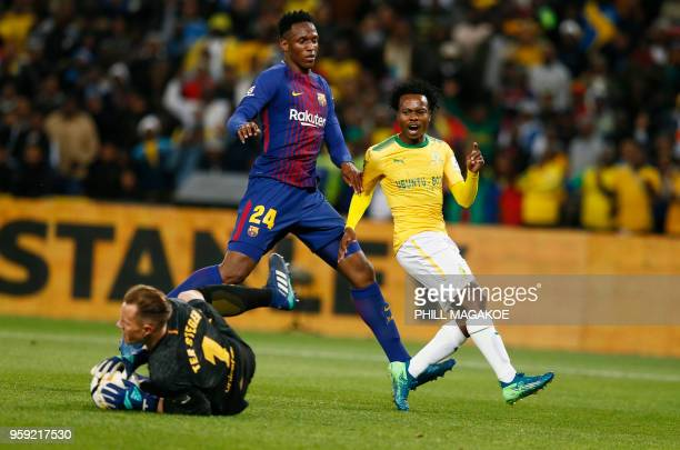 Barcelona goalkeeper MarcAndre ter Stegen makes a save while defender Yerry Minais tackles Mamelodi Sundown forward Percy Tau during their friendly...