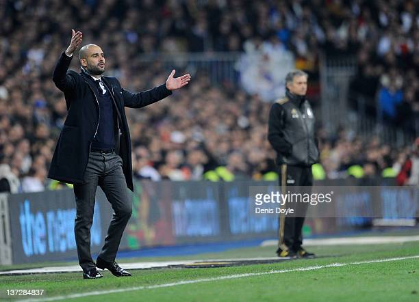 Barcelona head coach Josep Guardiola directs his team while Real Madrid head coach Jose Mourinho looks on during the Copa del Rey Quarter Finals...