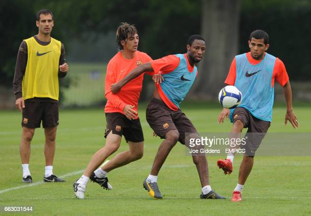 Barcelona manager Josep 'Pep' Guardiola watches over David Corcoles Alvaraz Seydou Keita and Dani Alves in training