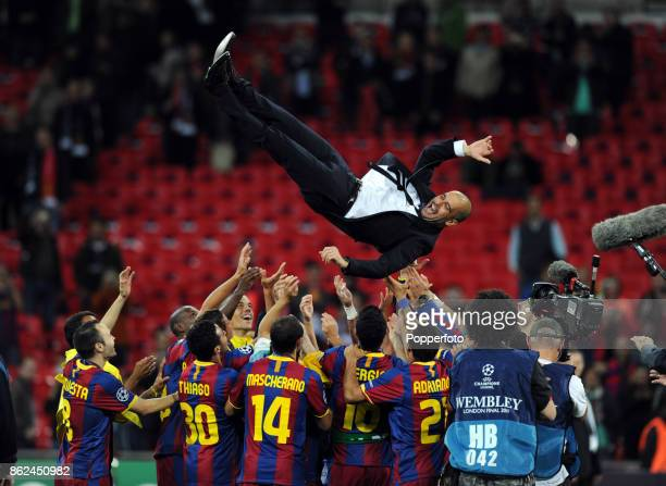 Barcelona manager Pep Guardiola is thrown in the air by his team as they celebrate after winning the UEFA Champions League Final against Manchester...