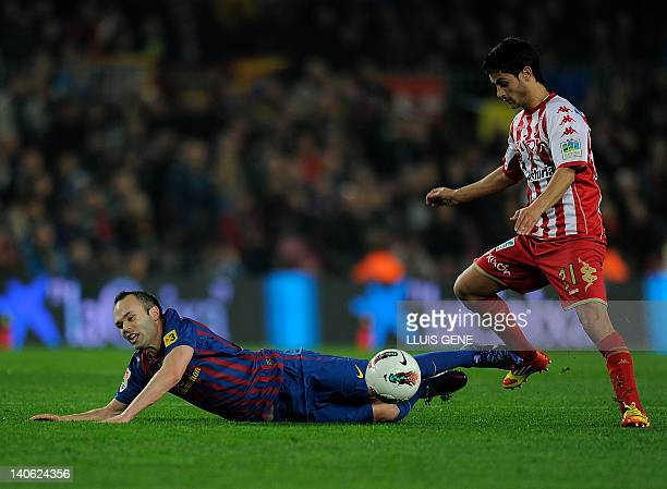 Barcelona midfielder Andres Iniesta fights for the ball with Sporting Gijon defender Alex Menendez on March 3 2012 during a Spanish league football...