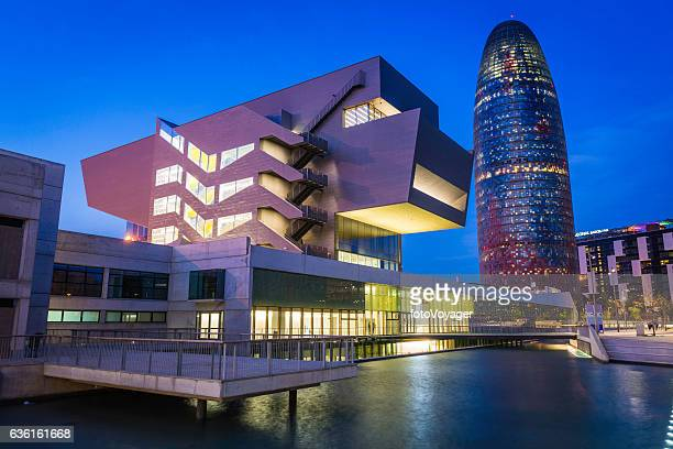 barcelona museu del disseny torre agbar iconic landmarks illuminated spain - barcelona spain stock photos and pictures