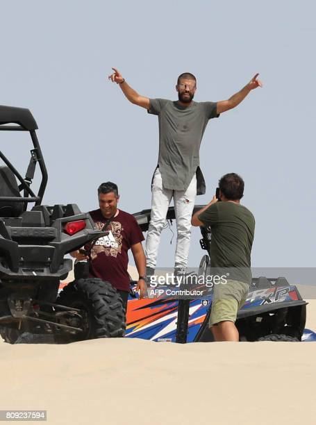 Barcelona player Gerard Pique poses for a photo during a visit to the Saylayn dunes south of Doha on July 5 2017 / AFP PHOTO / STRINGER