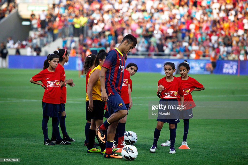 FC Barcelona player Neymar is watched by local children during a training session on August 4, 2013 in Tel Aviv, Israel. Members of the FC Barcelona squad have travelled to the Middle East to visit Israel and the West Bank as part of a two-day 'peace tour'.