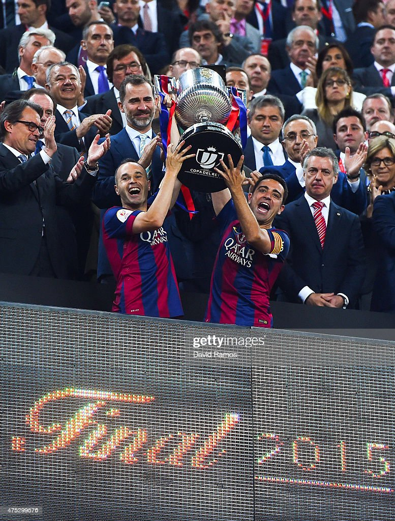 FC Barcelona players Andres Iniesta (L) and Xavi Hernandez of FC Barcelona celebrate with the trophy after winning the Copa del Rey Final match between FC Barcelona and Athletic Club at Camp Nou on May 30, 2015 in Barcelona, Spain.