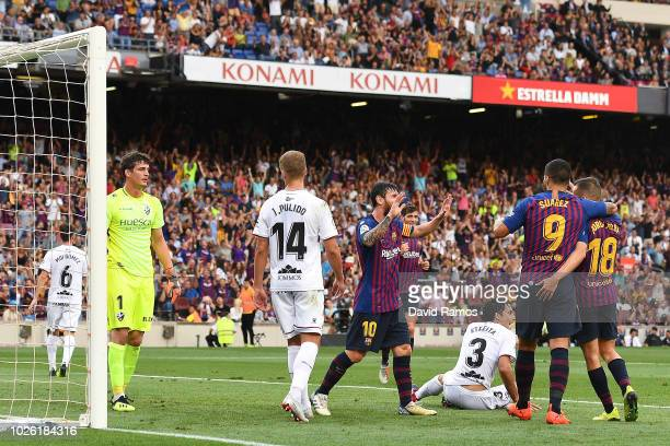Barcelona players celebrate after Jorge Pulido of SD Huesca scored an own goal during the La Liga match between FC Barcelona and SD Huesca at Camp...