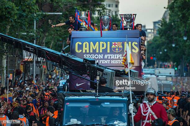 Barcelona players celebrate on an open top bus during their victory parade after winning the UEFA Champions League Final on June 7 2015 in Barcelona...
