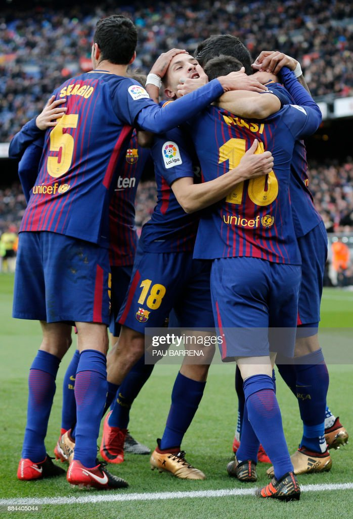 Barcelona players celebrate their second goal during the Spanish league football match FC Barcelona vs RC Celta de Vigo at the Camp Nou stadium in Barcelona on December 2, 2017. / AFP PHOTO / Pau Barrena