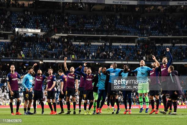 Barcelona players celebrate their win at the end of the Spanish league football match between Real Madrid CF and FC Barcelona at the Santiago...