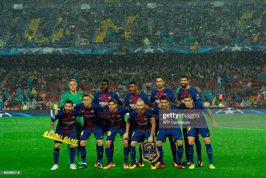 Barcelona players line up in the rain before the the UEFA Champions League group D football match FC Barcelona vs Olympiacos FC at the Camp Nou stadium in Barcelona on Ocotber 18, 2017. /