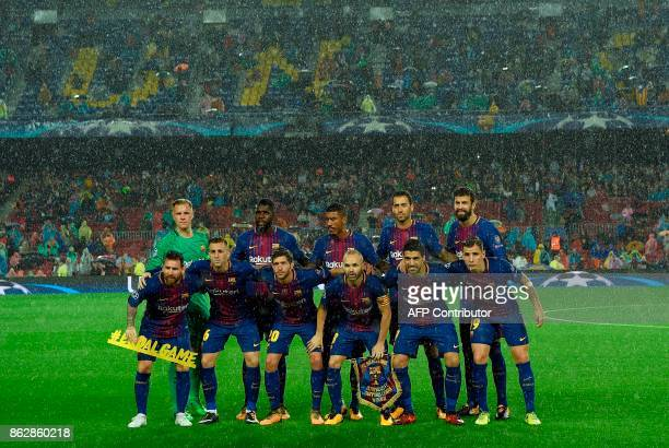 Barcelona players line up in the rain before the the UEFA Champions League group D football match FC Barcelona vs Olympiacos FC at the Camp Nou...