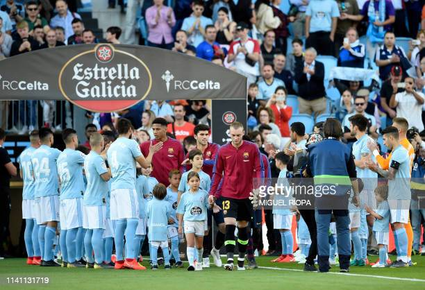 Barcelona players new champions of La Liga walk through a passageway formed by Celta de Vigo players before the Spanish league football match between...