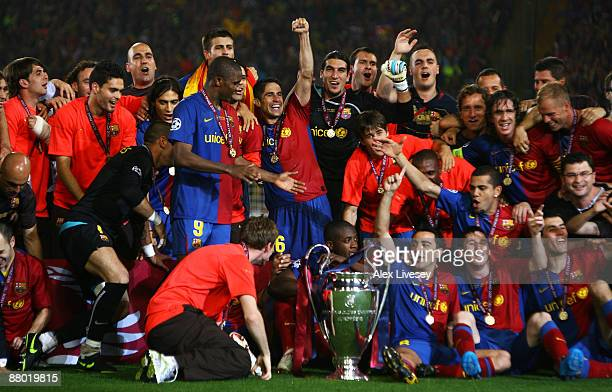 Barcelona players pose in front of the trophy after they celebrate winning the UEFA Champions League Final match between Barcelona and Manchester...