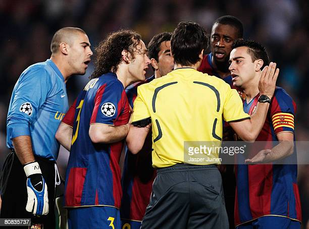 Barcelona players surround the referee Massimo Busacca as his gives Manchester United a penalty early in the UEFA Champions League Semi-Final, first...