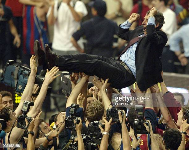 Barcelona players throw their coach, Svetislav Pesic, in the air to celebrate beating Benetton Treviso in the Euroleague Final Four match in Palau...