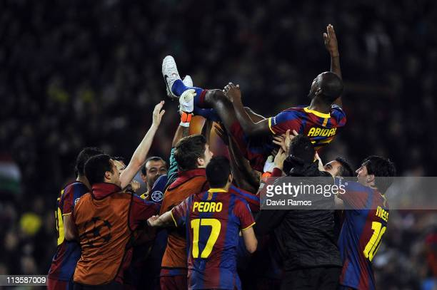 Barcelona players toss teammate Eric Abidal up in the air after defeating Real Madrid in the UEFA Champions League Semi Final second leg match...