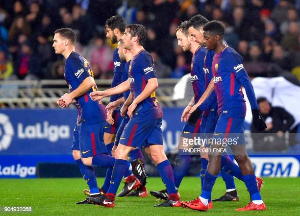 Barcelona players walk together after their third goal during the Spanish league football match between Real Sociedad and FC Barcelona at the Anoeta...