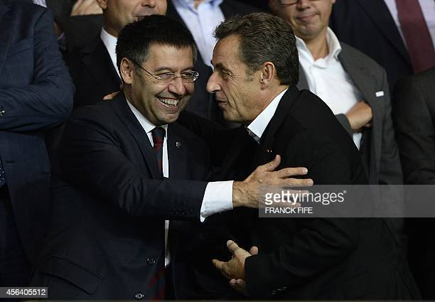 Barcelona president Josep Maria Bartomeu embraces former French president Nicolas Sarkozy as they attend the UEFA Champions League football match...