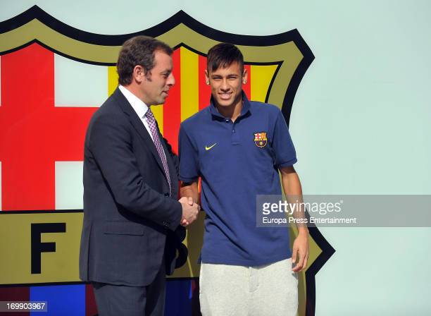 Barcelona President Sandro Rosell and Neymar shake hands as they pose for the media during the official presentation as a new player of the FC...