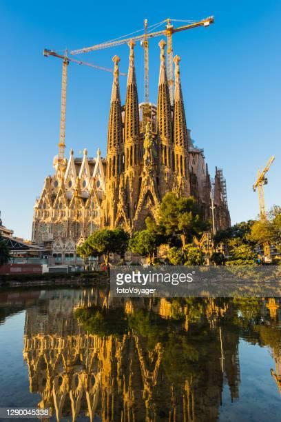 barcelona sagrada familia ikonische gaudi kathedrale türme reflektiert see spanien - familia stock-fotos und bilder