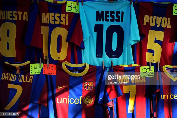 Barcelona shirts wearing the names of players Lionel Messi David Villa Andres Iniesta and Carles Puyol hang in one of the shops surrounding the Camp...