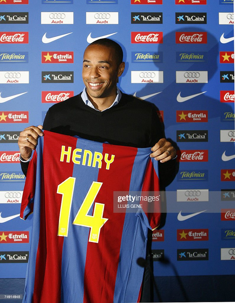 cb0c3b613 Arsenal s Thierry Henry poses with his new shirt after being ...
