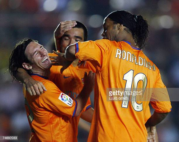Barcelona's Argentinian Leo Messi celebrates with Brazilian Ronaldinho and Portuguese Deco after scoring his second goal against Gimnastic Tarragona...