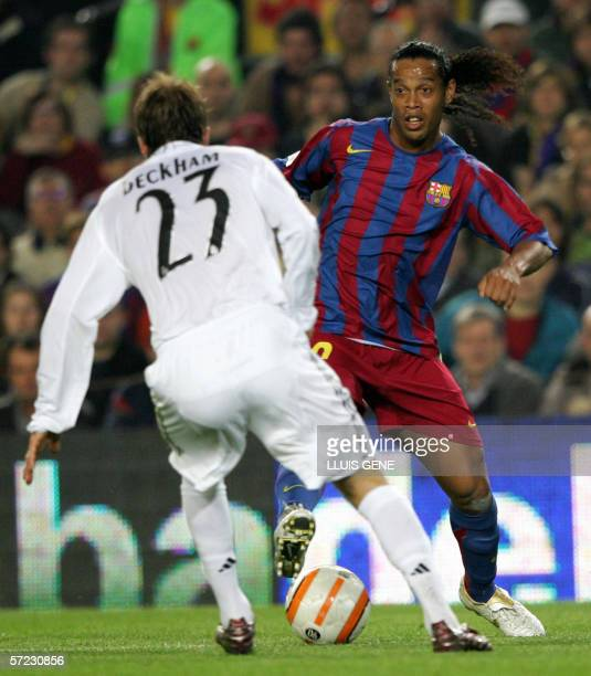 Barcelona's Brazilian Ronaldinho tries to get round Real Madrid's David Beckham during their Spanish league football match at the Camp Nou stadium in...