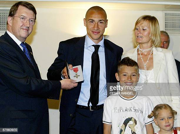 Barcelona's Swedish striker Henrik Larsson poses with his wife Magdalena daughter Janele and son Jordan as he holds the Order of the British Empire...