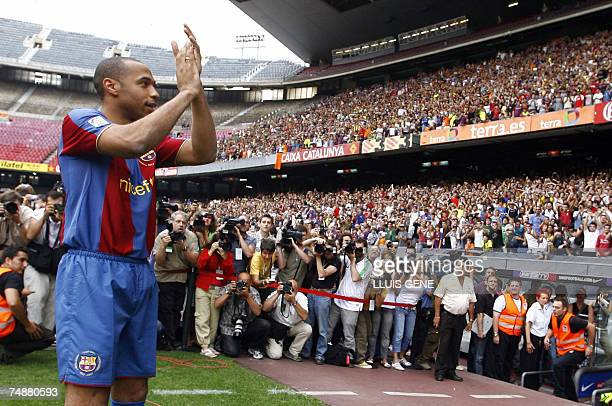 Former Arsenal forward Thierry Henry is applauded by fans as he poses during his unveiling at Barcelona's Camp Nou stadium 25 June 2007 Barcelona...
