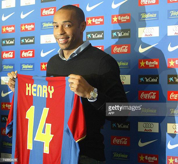 Former Arsenal forward Thierry Henry poses with his new shirt during his unveiling at Barcelona's Camp Nou stadium 25 June 2007 Barcelona are...