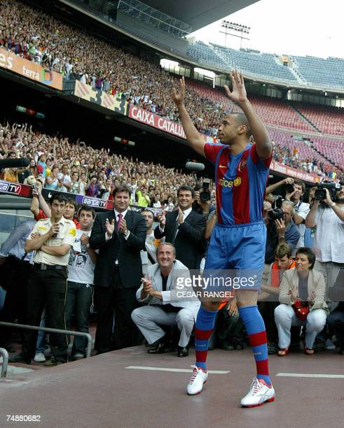 Former Arsenal forward Thierry Henry waves to fans during his unveiling at Barcelona's Camp Nou stadium 25 June 2007 Barcelona agreed a fouryear deal...