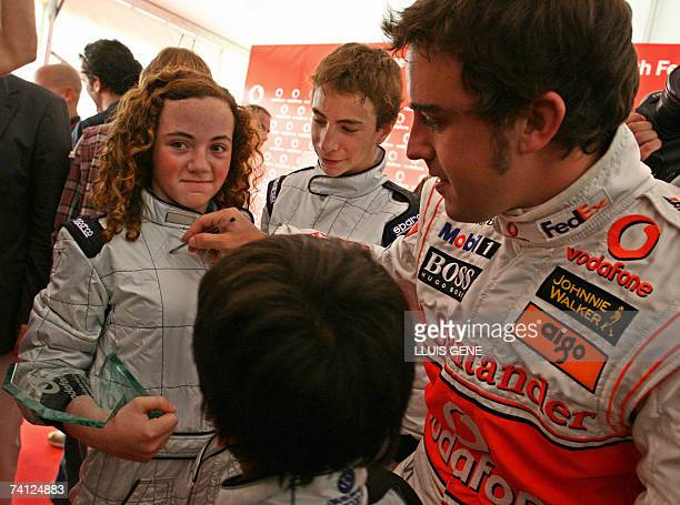 McLaren's Spanish Formula One driver Fernando Alonso signs autographs after taking part in an exhibition gocart race at a carting track in Montmelo...