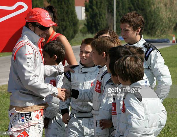 McLaren's Spanish Formula One driver Fernando Alonso talks with young drivers after taking part in an exhibition gocart race at a carting track in...