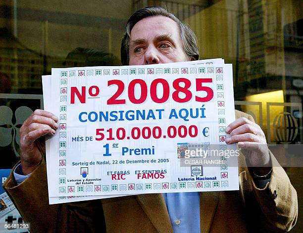 The owner of a lottery shop poses with the Spanish Christmas lottery ticket number 20085 in Vic 22 December 2005 Lucky Spanish ticketholders 22...