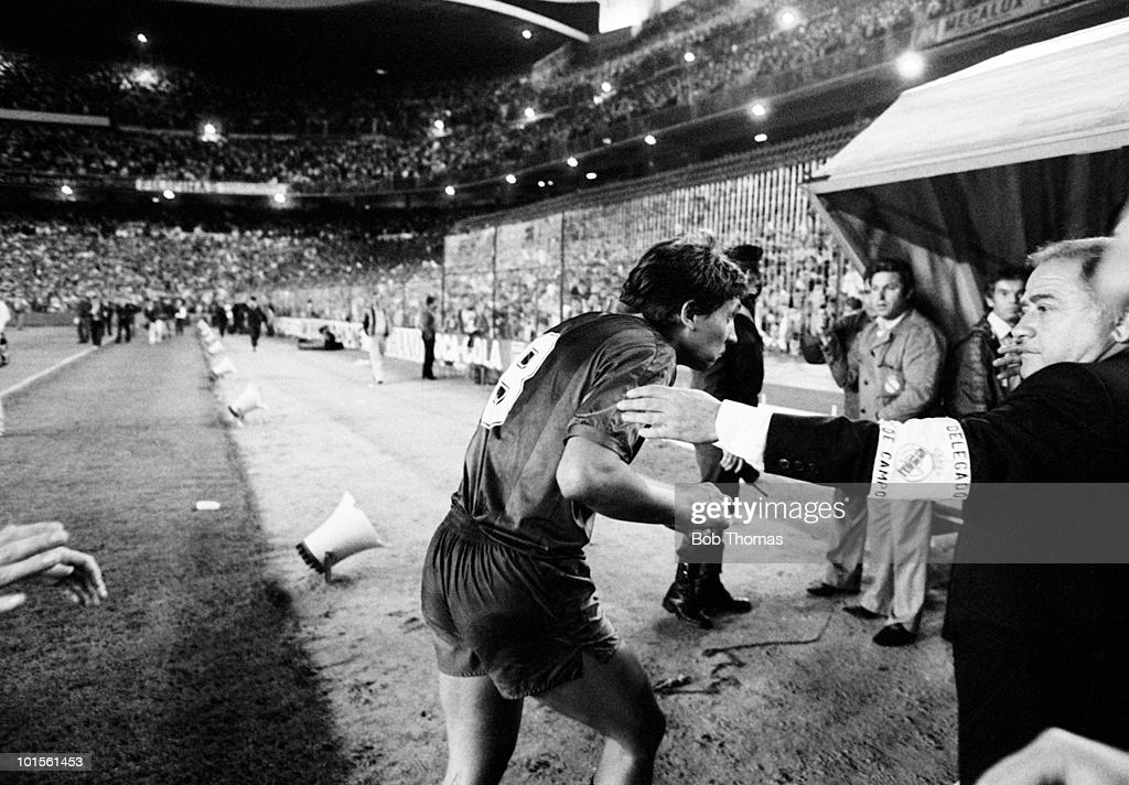 Barcelona striker Gary Lineker heads for the safety of the tunnel entrance as missles rain down from Real Madrid's fans at the end of the Spanish League match held at Santiago Bernabeu Stadium in Madrid on 8th October 1986. The match ended in a 1-1 draw. (Bob Thomas/Getty Images).