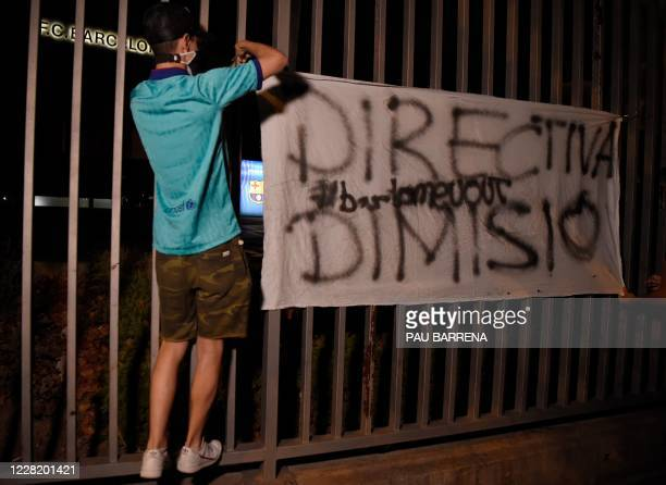 Barcelona supporter hangs a banner demanding the club's board of directors to resign outside the club's headquarters in Barcelona, on August 25...