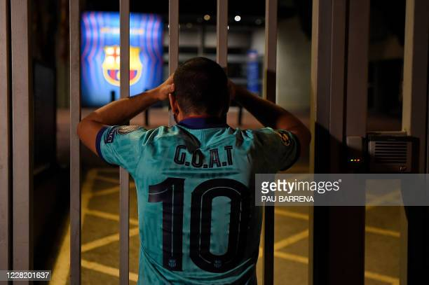 Barcelona supporter sporting a jersey with the acronym of Greatest of all times and number 10 of Barcelona's Argentinian forward Lionel Messi looks...