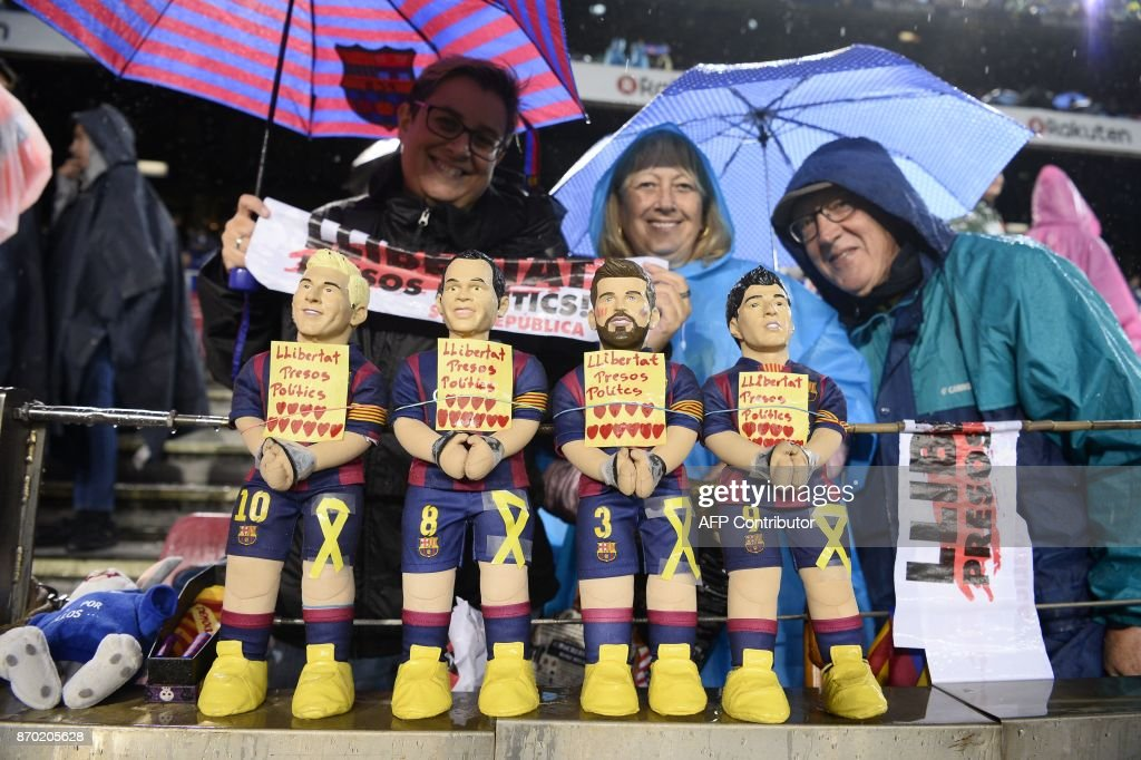 Barcelona supporters display figurines of (L-R) Barcelona's Argentinian forward Lionel Messi, Barcelona's Spanish midfielder Andres Iniesta, Barcelona's Spanish defender Gerard Pique and Barcelona's Uruguayan forward Luis Suarez with their hands tied and reading 'Freedom to the political prisoners' in reference to detained Catalan officials during the Spanish league football match FC Barcelona vs Sevilla FC at the Camp Nou stadium in Barcelona on November 4, 2017. / AFP PHOTO / Josep LAGO