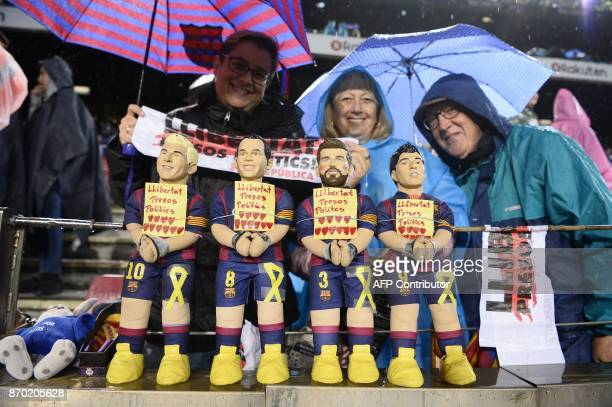 Barcelona supporters display figurines of Barcelona's Argentinian forward Lionel Messi Barcelona's Spanish midfielder Andres Iniesta Barcelona's...