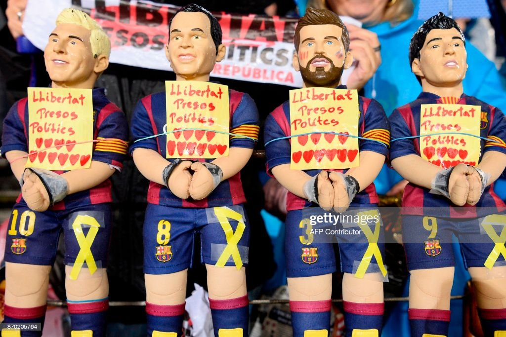 TOPSHOT - Barcelona supporters display figurines of (L-R) Barcelona's Argentinian forward Lionel Messi, Barcelona's Spanish midfielder Andres Iniesta, Barcelona's Spanish defender Gerard Pique and Barcelona's Uruguayan forward Luis Suarez with their hands tied and reading 'Freedom to the political prisoners' in reference to detained Catalan officials during the Spanish league football match FC Barcelona vs Sevilla FC at the Camp Nou stadium in Barcelona on November 4, 2017. / AFP PHOTO / Josep LAGO