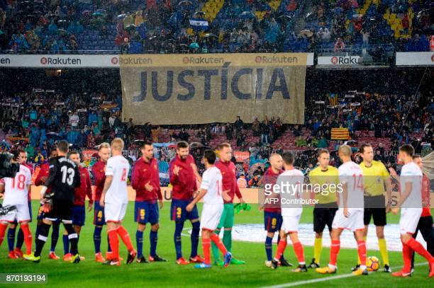 Barcelona supporters hold a banner reading 'Justice' in reference to the Catalan political crisis and the detention of Catalan leaders as players...