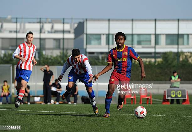 Barcelona youth player controls the ball besides a youth player from Vilassar de Mar on one of the pitches at the Joan Camper training ground on...
