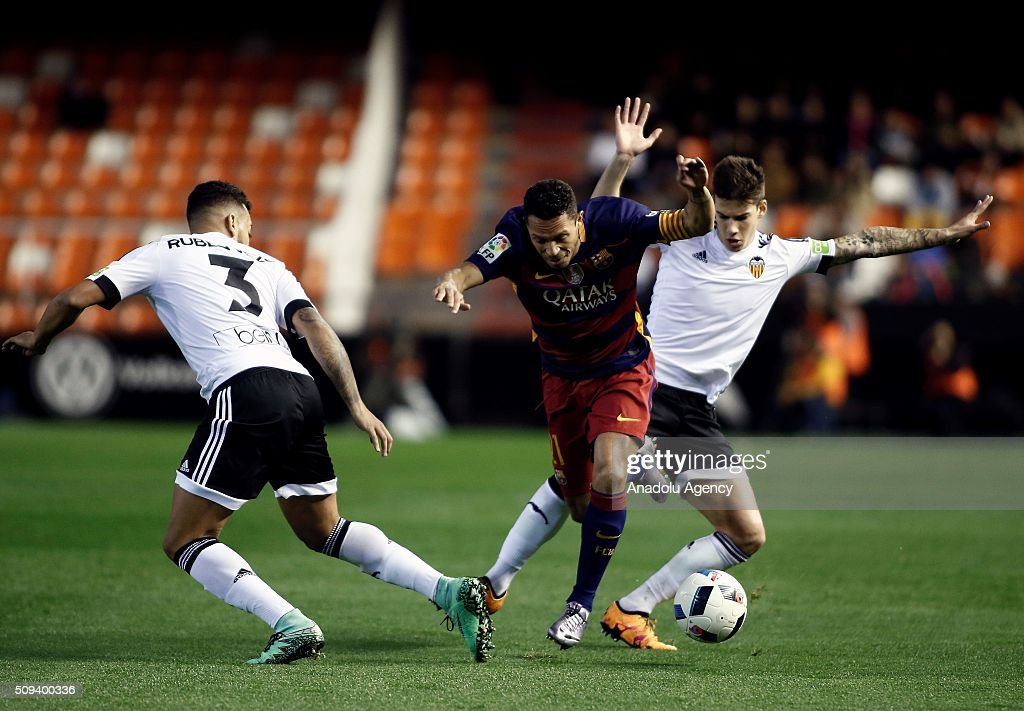 Barcelona's Adriano Correia (C) and Valencia's Ruben Vezo (L) in action during the Spanish Copa del Rey (King's Cup) semifinals second leg football match between Valencia and FC Barcelona at the Mestalla Stadium in Valencia, Spain on February 10, 2016.