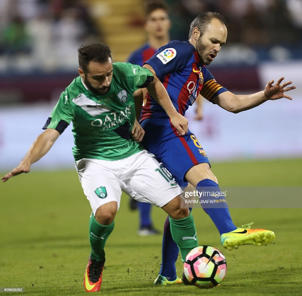 FC Barcelona's Andres Iniesta vies for the ball with Al-Ahly's Giannis Fetfatzidis during a friendly football match between FC Barcelona and Saudi Arabia's Al-Ahli FC on December 13, 2016 in the Qatari capital Doha. Goals from Luiz Suarez, Lionel Messi and Neymar helped Barcelona beat Saudi champions Al-Ahli 5-3 in a thrilling friendly in Doha. The superstar trio all scored by the 17th minute, helping the Spanish giants to stroll into an early three-goal lead. JAAFAR