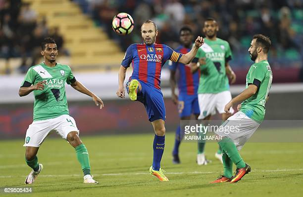FC Barcelona's Andres Iniesta vies for the ball with AlAhly's Waleed Bakshween and Giannis Fetfatzidis during a friendly football match between FC...