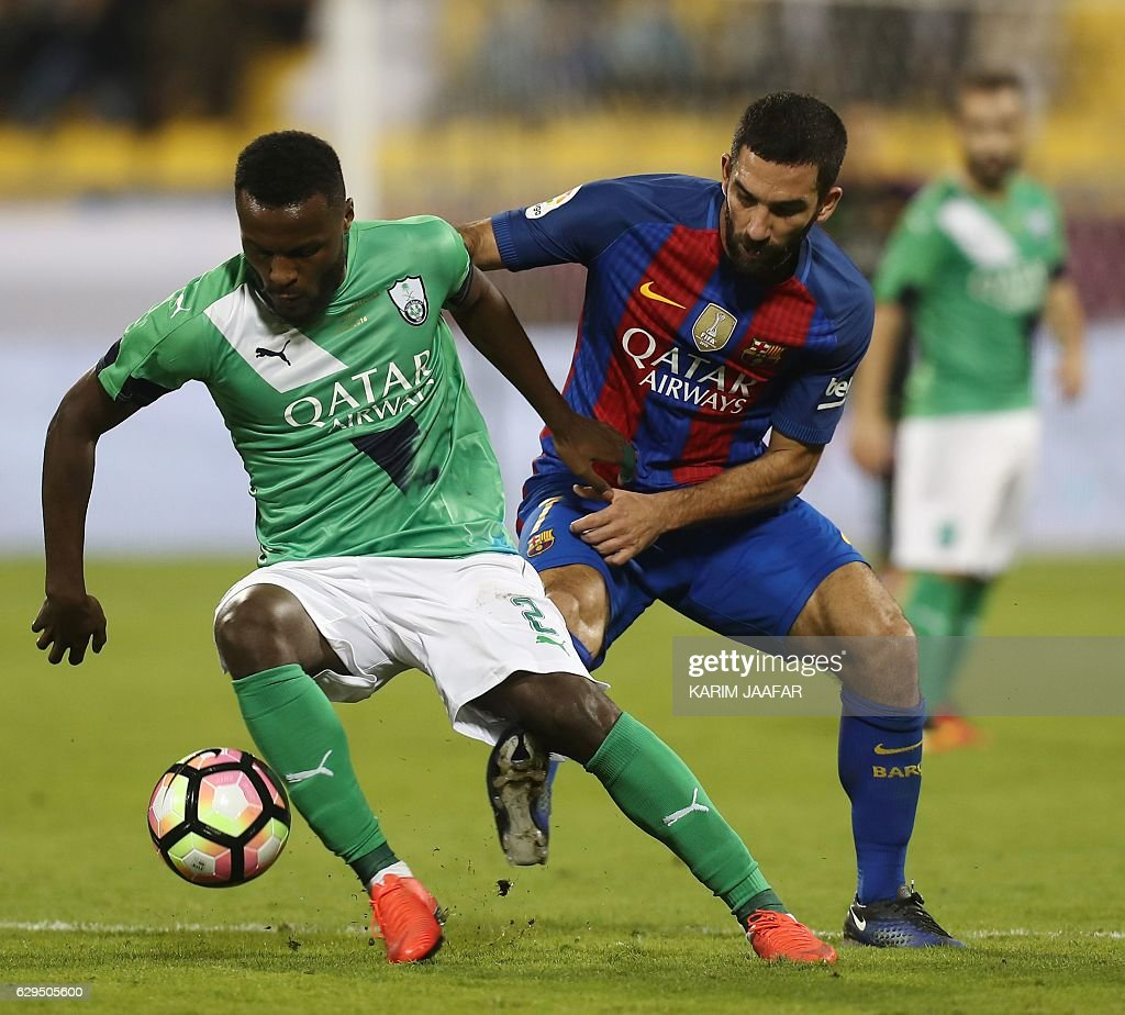 FC Barcelona's Arda Turan vies for the ball with Al-Ahly's Ali al-Zubaidi during a friendly football match between FC Barcelona and Saudi Arabia's Al-Ahli FC on December 13, 2016 in the Qatari capital Doha. Goals from Luiz Suarez, Lionel Messi and Neymar helped Barcelona beat Saudi champions Al-Ahli 5-3 in a thrilling friendly in Doha. The superstar trio all scored by the 17th minute, helping the Spanish giants to stroll into an early three-goal lead. JAAFAR