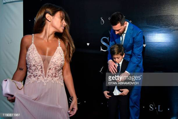 Barcelona's Argentine forward Lionel Messi buttons the blazer of his son Thiago up as his wife Antonella Roccuzzo looks on, upon arriving at a party...