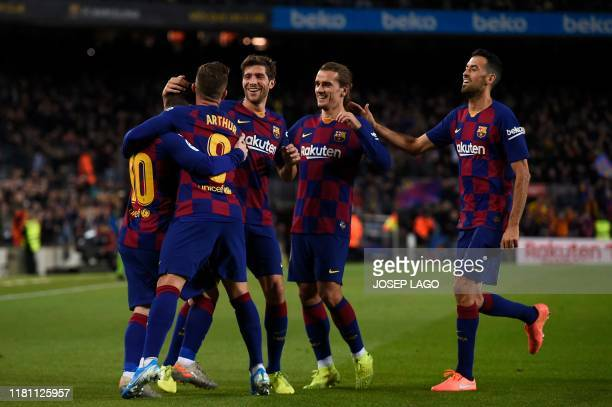 Barcelona's Argentine forward Lionel Messi celebrates with Barcelona's Spanish defender Sergi Roberto, Barcelona's Brazilian midfielder Arthur,...